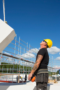 Sweden, Ostergotland, Linkoping, Construction worker looking at crane lifting building blockの写真素材 [FYI02194019]