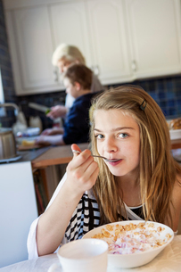 Portrait of girl (12-13) eating breakfastの写真素材 [FYI02194075]