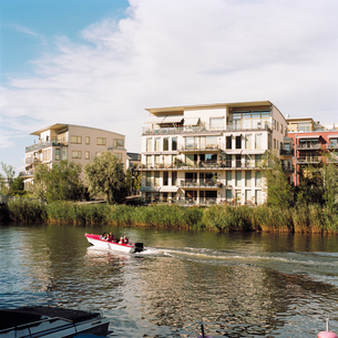 Sweden, Sodermanland, Stockholm, Hammarby Sjostad, Canal front townhouse and motor boatの写真素材 [FYI02194079]