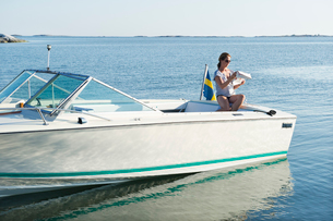 Sweden, Sodermanland, Stockholm Archipelago, Varmdo, Norsten, Woman reading newspaper on motor boatの写真素材 [FYI02194109]