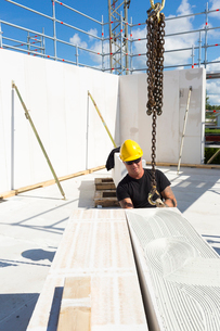 Sweden, Ostergotland, Linkoping, Construction worker preparing building block to be liftedの写真素材 [FYI02194378]