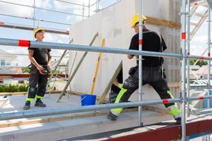 Sweden, Ostergotland, Linkoping, Construction workers preparing building blocks to build wallの写真素材 [FYI02194389]