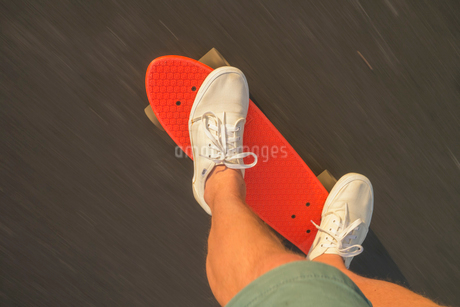 Sweden, Smaland, Anderstorp, Low-section shot of skater riding red shortboardの写真素材 [FYI02194421]