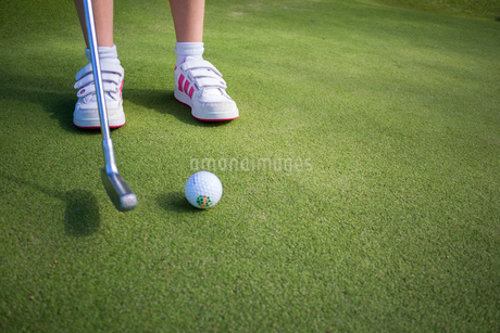 Sweden, Vastergotland, Low-section shot of girl (8-9) about to swing golf ball off artificial turfの写真素材 [FYI02194431]
