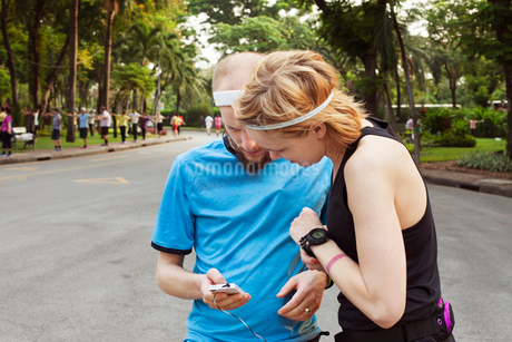 Thailand, Bangkok, Man and woman checking device after joggingの写真素材 [FYI02194615]