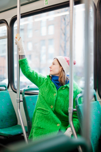 Finland, Helsinki, Young woman pressing request stop button in tramの写真素材 [FYI02194793]