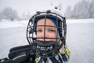 Finland, Pohjois-Pohjanmaa, Oulu, Portrait of boy (6-7) in ice hockey helmetの写真素材 [FYI02194896]