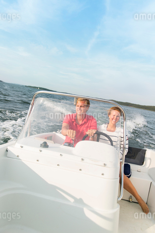 Sweden, Sodermanland, Young couple on motorboatの写真素材 [FYI02194970]