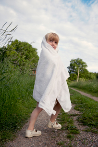 Sweden, Mariefred, Girl standing wrapped in towelの写真素材 [FYI02194980]