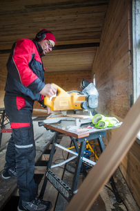 Finland, Carpenter working with electric sawの写真素材 [FYI02195204]