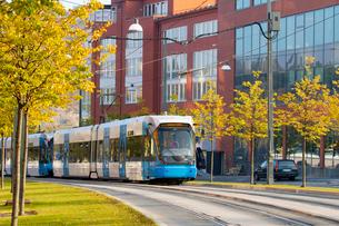 Sweden, Stockholm, Hammarby Sjostad, Tram riding along city street in autumnの写真素材 [FYI02195424]
