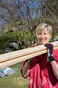 Sweden, Sodermanland, Nacka, Woman carrying planksの写真素材 [FYI02195535]