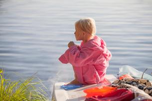 Sweden, Smaland, Girl (6-7) sitting in bathrobeの写真素材 [FYI02195604]