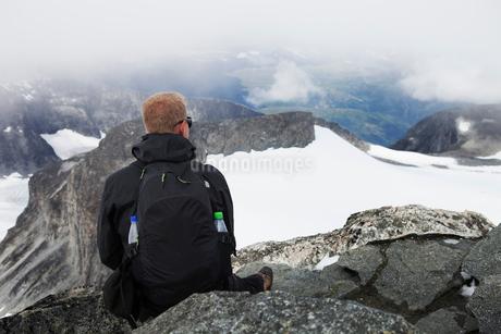 Norway, Jotunheimen, Bovertun, Hiker looking at mountainsの写真素材 [FYI02195677]