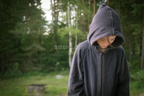 Sweden, Vastergotland, Lerum, Girl in sweatshirt looking at lakeshoreの写真素材 [FYI02196067]