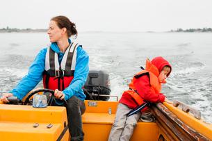 Sweden, Uppland, Runmaro, Barrskar, Mother and son (4-5) on motor boatの写真素材 [FYI02196110]