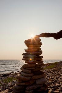 Sweden, Oland, Gronhogen, Boy (10-11) putting last stone onto stone heapの写真素材 [FYI02196127]
