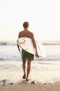 Costa Rica, Santa Teresa, Teenager (16-17) with surfboard walking towards seaの写真素材 [FYI02196223]