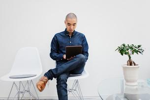 Sweden, Freelancer sitting with digital tabletの写真素材 [FYI02196255]