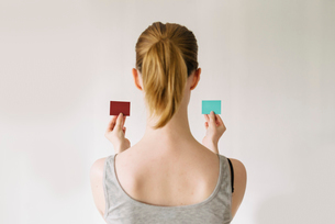 Sweden, Woman comparing color swatches against wall, rear viewの写真素材 [FYI02196417]