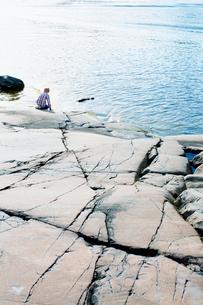 Sweden, Uppland, Oregrund, Boy (8-9) touching cold sea waterの写真素材 [FYI02196477]