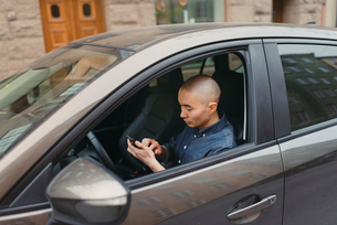 Sweden, Sodermanland, Stockholm, Sodermalm, Young man using smart phone in carの写真素材 [FYI02196545]