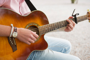 Sweden, Uppland, Danderyd, Young man playing acoustic guitar, mid sectionの写真素材 [FYI02196562]