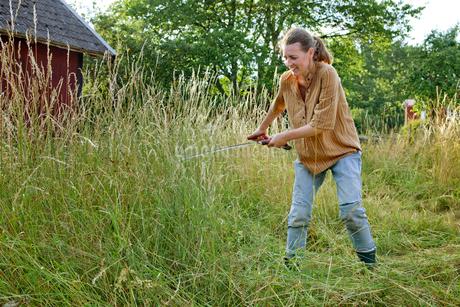 Sweden, Smaland, Alsterbro, Female farmer cutting grassの写真素材 [FYI02196569]