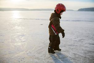Sweden, Vastergotland, Lerum, Lake Aspen, Girl (6-7) learning how to ice skateの写真素材 [FYI02196629]