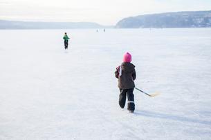 Sweden, Vastergotland, Lerum, Lake Aspen, Siblings (6-7, 8-9) playing ice hockey on lakeの写真素材 [FYI02196647]
