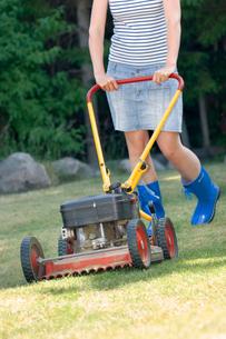 Sweden, Bohuslan, Tjorn, Woman mowing lawnの写真素材 [FYI02196745]