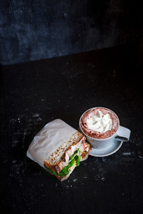 Cup of hot chocolate and sandwich in dark roomの写真素材 [FYI02196949]
