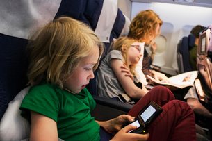 Sweden, Mother travelling by plane with children (6-7, 10-11)の写真素材 [FYI02197069]