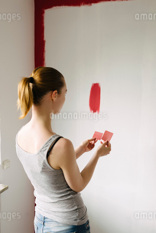 Sweden, Woman comparing color swatches against wallの写真素材 [FYI02197088]