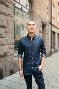 Sweden, Sodermanland, Stockholm, Sodermalm, Smiling young man on sidewalkの写真素材 [FYI02197229]