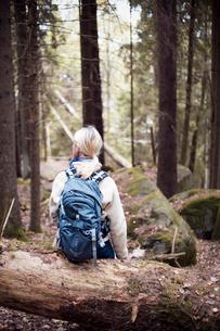 Sweden, Vastergotland, Lerum, Female backpacker sitting on trunk of fallen tree in forestの写真素材 [FYI02197239]