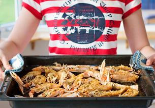 Sweden, Bohuslan, Woman holding hot baking pan with norway lobster (Nephrops norvegicus)の写真素材 [FYI02197361]