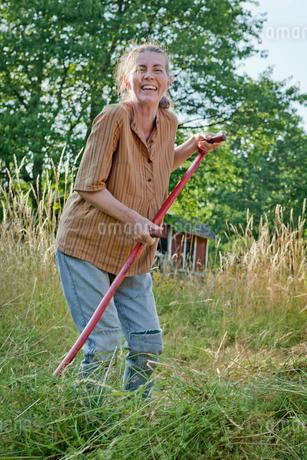 Sweden, Smaland, Alsterbro, Female farmer cutting grassの写真素材 [FYI02197484]