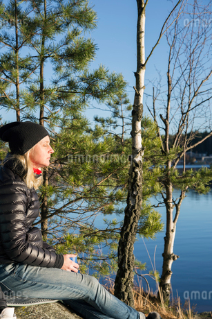 Sweden, Vastergotland, Lerum, Female hiker relaxing on lakeshoreの写真素材 [FYI02197611]