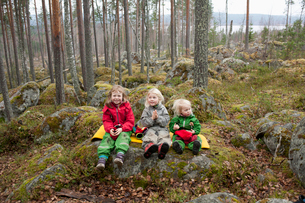 Finland, Mellersta Finland, Jyvaskyla, Three sisters (2-3 and 6-7) sitting on yellow ground pad in fの写真素材 [FYI02197793]