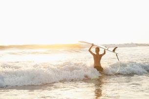 Costa Rica, Santa Teresa, Teenager (14-15) with surfboard wading in seaの写真素材 [FYI02197818]