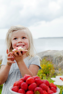 Sweden, Uppland, Roslagen, Girl (6-7) eating strawberry dessert outdoorsの写真素材 [FYI02197916]