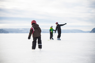 Sweden, Vastergotland, Lerum, Lake Aspen, Mom playing ice hockey with her two children (6-7, 8-9) onの写真素材 [FYI02198025]