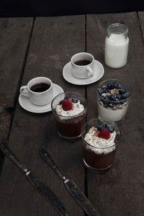 Two coffee cups and jar with milk served with fruit dessertの写真素材 [FYI02198044]