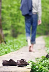 Sweden, Vastergotland, Goteborg, Man walking barefoot through forestの写真素材 [FYI02198082]