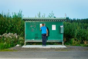 Finland, Jaala, Man watching timetable at bus stop in summertimeの写真素材 [FYI02198098]