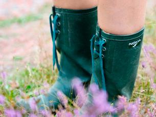 Sweden, Bohuslan, Tjorn, Woman wearing rubber boots in meadowの写真素材 [FYI02198146]