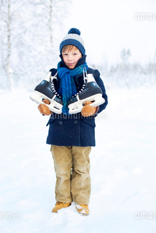 Finland, Keski-Suomi, Aanekoski, Portrait of young boy (8-9) with ice skatesの写真素材 [FYI02198328]