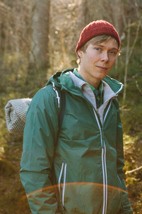 Finland, Esbo, Kvarntrask, Portrait of young man wearing woolly hat and windcheater jacket in forestの写真素材 [FYI02198433]