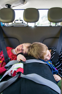 Boys (2-3, 4-5) sleeping in carの写真素材 [FYI02198487]
